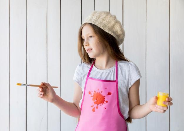Primer plano de una hermosa niña con pintura amarilla y pincel en la mano de pie contra la pared de madera