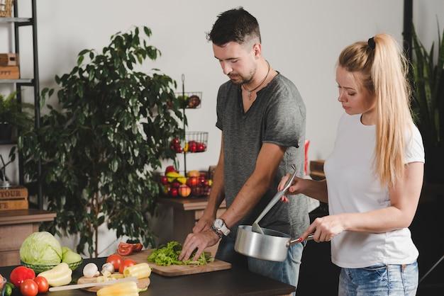Primer plano de hermosa pareja preparando comida en la cocina