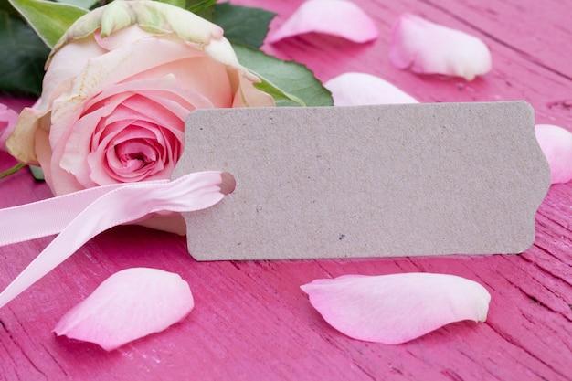 Primer plano de una hermosa rosa rosa y pétalos sobre una superficie de madera rosa con una tarjeta con espacio para texto