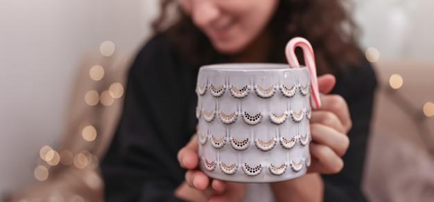 Primer plano de una hermosa taza de navidad en manos femeninas sobre un fondo borroso.