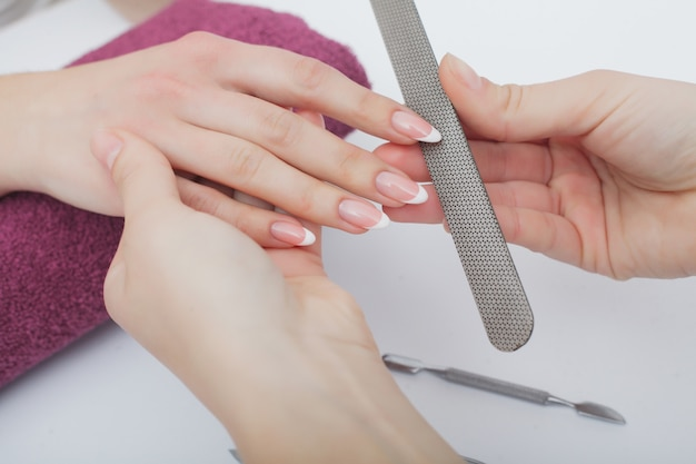 Primer plano de hermosas manos femeninas con manicura spa en salón de belleza