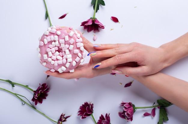 Primer plano de hermosas manos femeninas sofisticadas con flores rosas y donut sobre una mesa blanca. concepto de cuidado de manos, crema antiarrugas, antienvejecimiento, spa.