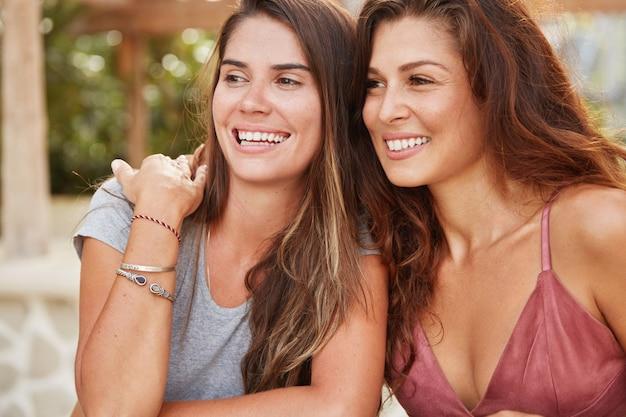 Primer plano de hermosas mujeres jóvenes con piel bronceada sana y dientes perfectos blancos