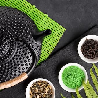 Primer plano de hierba seca saludable y polvo de té matcha sobre fondo de piedra pizarra