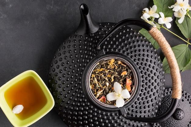 Primer plano de la hierba de té seco y tetera de cerámica