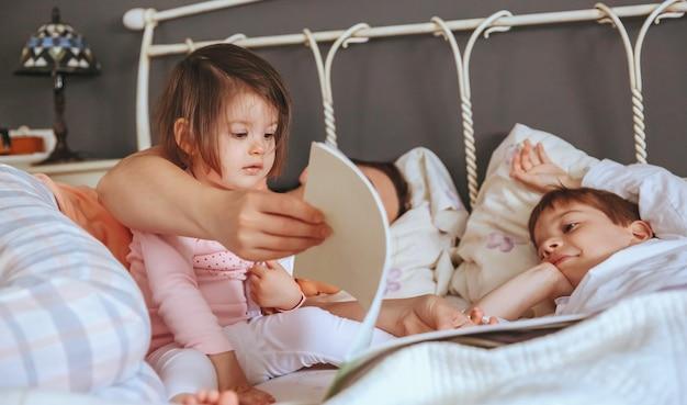 Primer plano de una hija leyendo un libro de cuentos con su madre y su hermano en la cama. concepto de tiempo de ocio familiar de fin de semana.