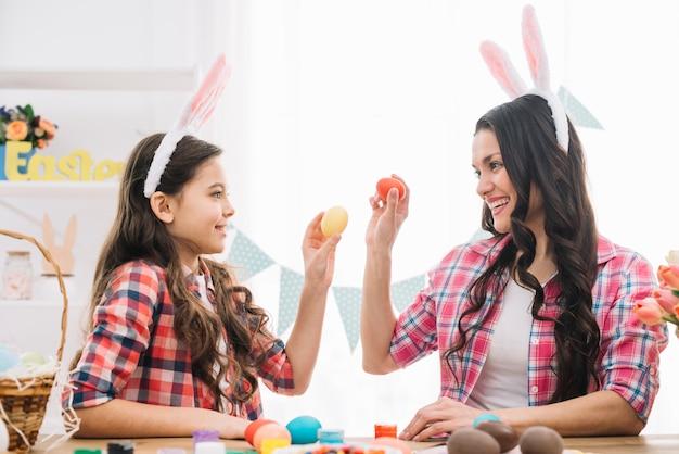 Primer plano de una hija y su madre mostrando los huevos de pascua entre sí