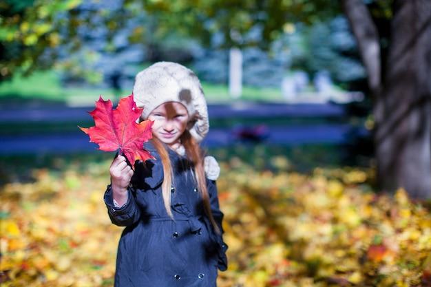 Primer plano de la hoja de arce roja en manos de la niña en el hermoso día de otoño