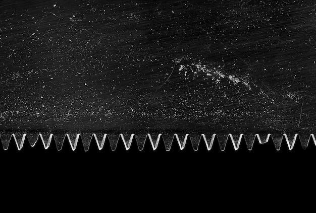 Primer plano de una hoja de sierra sucia aislada en negro