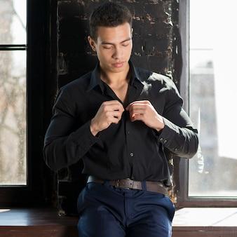 Primer plano de un hombre abotonando la camisa negra de pie cerca de la ventana