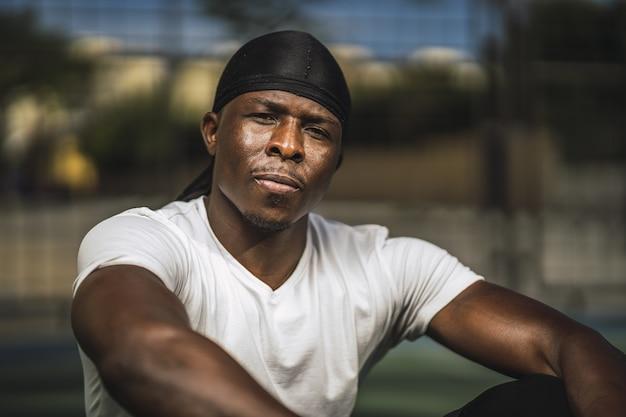 Primer plano de un hombre afroamericano con una camisa blanca sentado en la cancha de baloncesto