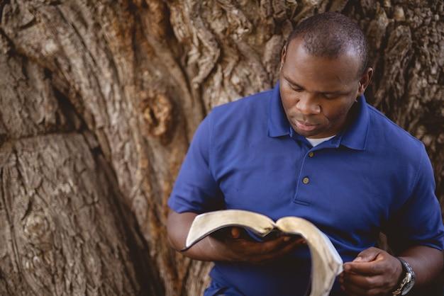 Primer plano de un hombre afroamericano leyendo una biblia con un árbol