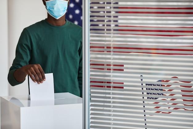 Primer plano del hombre afroamericano en máscara poniendo la papeleta en la urna en el colegio electoral durante la pandemia