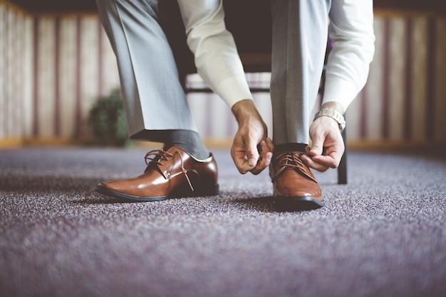 Primer plano de un hombre atando sus zapatos y preparándose para una reunión de negocios