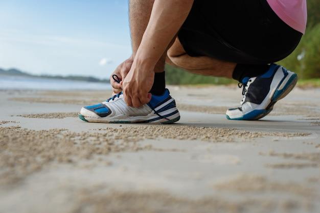 Primer plano de hombre atar cordones de los zapatos en la playa