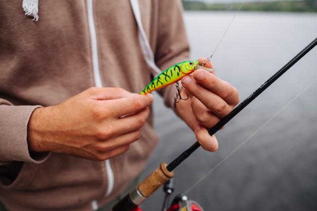 Primer plano del hombre atar señuelo en gancho de pesca