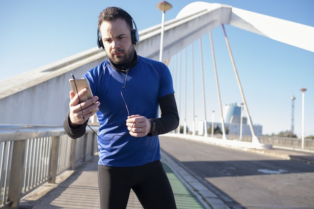 Primer plano de un hombre en auriculares azules usando su móvil mientras trota en la calle