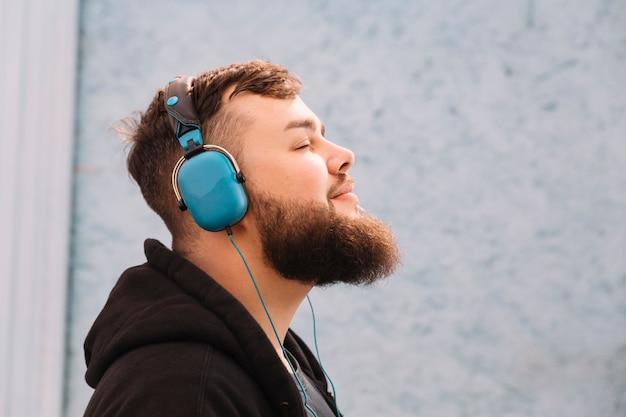 Primer plano, de, un, hombre, con, barba, escuchar música, en, auriculares