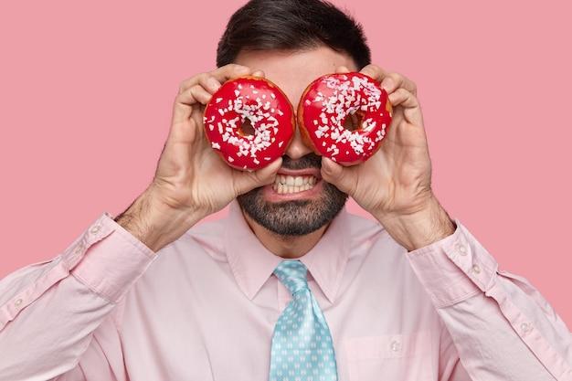 Primer plano de un hombre barbudo disgustado que aprieta los dientes, se cubre los ojos con donas, se viste formalmente, se para sobre la pared rosada