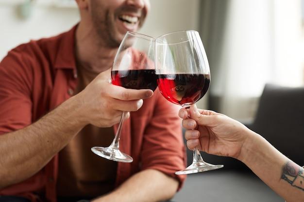 Primer plano del hombre brindando con una copa de vino con la mujer durante su cita