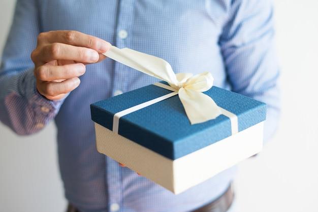Primer plano de hombre en camisa abriendo regalo de cumpleaños