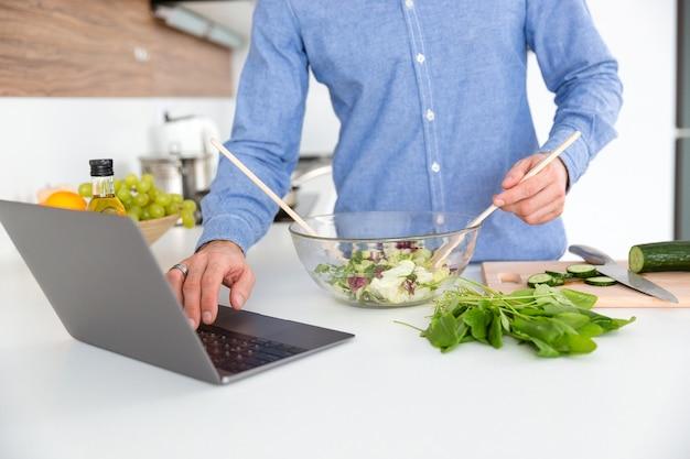 Primer plano de un hombre con camisa azul con ordenador portátil y hacer ensalada en un tazón de vidrio en la cocina