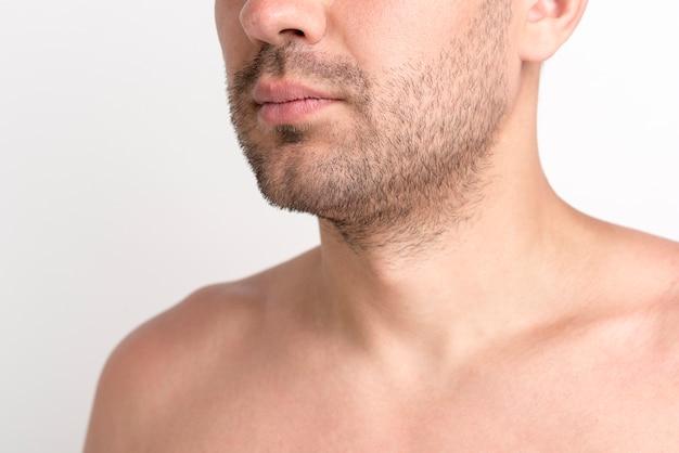 Primer plano del hombre sin camisa de rastrojo contra el fondo blanco.