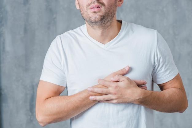 Primer plano de un hombre en camiseta blanca con dolor de corazón