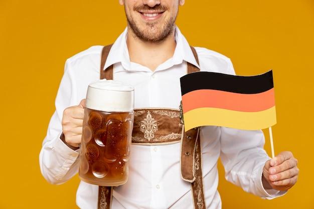 Primer plano del hombre con cerveza pinta y bandera