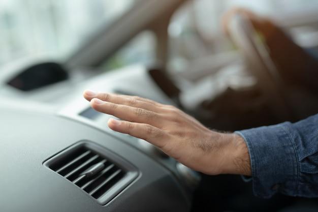 Primer plano de un hombre controlador de mano comprobando el ajuste de aire de acondicionamiento del sistema de refrigeración con flujo de aire frío en el coche