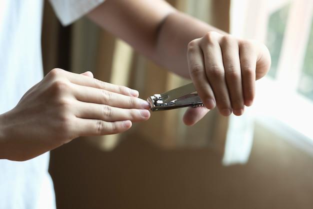 Primer plano de un hombre cortando uñas, concepto de salud