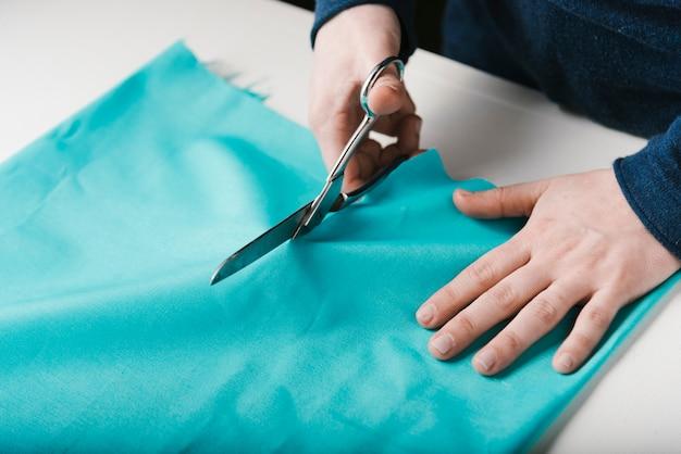 Primer plano del hombre cortando material azul