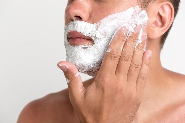Primer plano del hombre con crema de afeitar en la mejilla