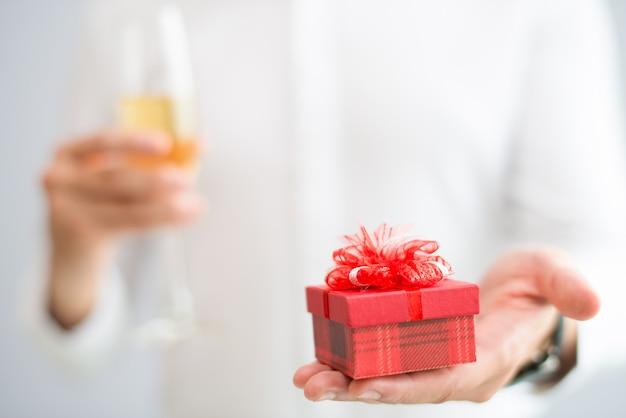 Primer plano del hombre dando una pequeña caja de regalo y sosteniendo el vaso