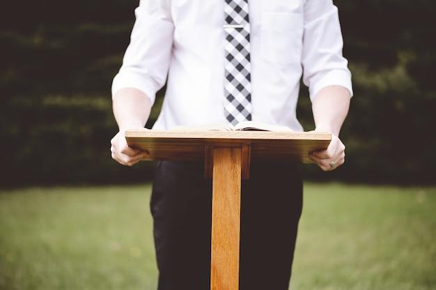 Primer plano de un hombre delante de un soporte de discurso con un libro abierto