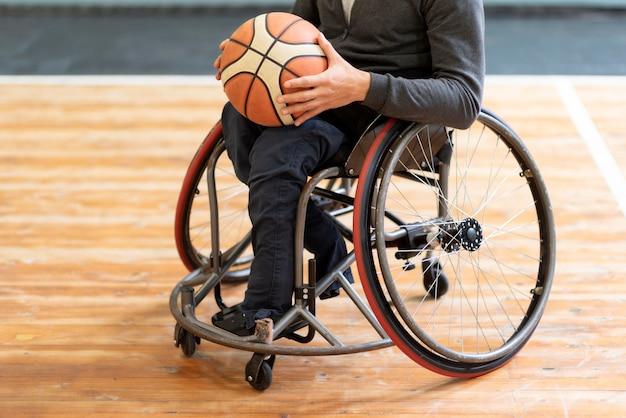 Primer plano, hombre discapacitado, tenencia, baloncesto