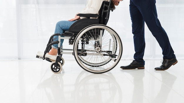 Primer plano de un hombre empujando a la mujer sentada en silla de ruedas