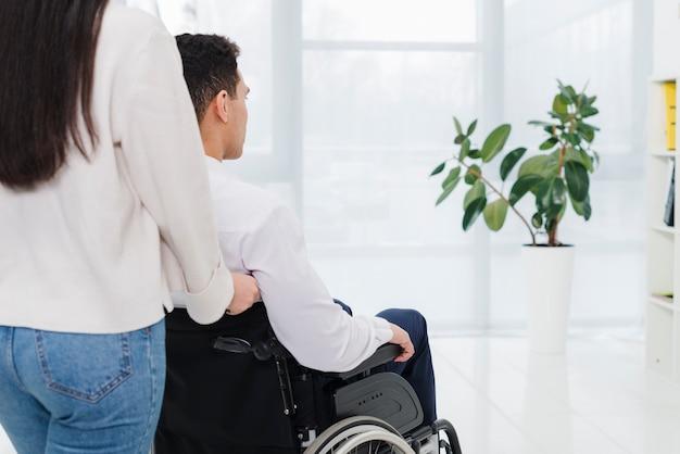 Primer plano de un hombre empujando a una mujer en silla de ruedas