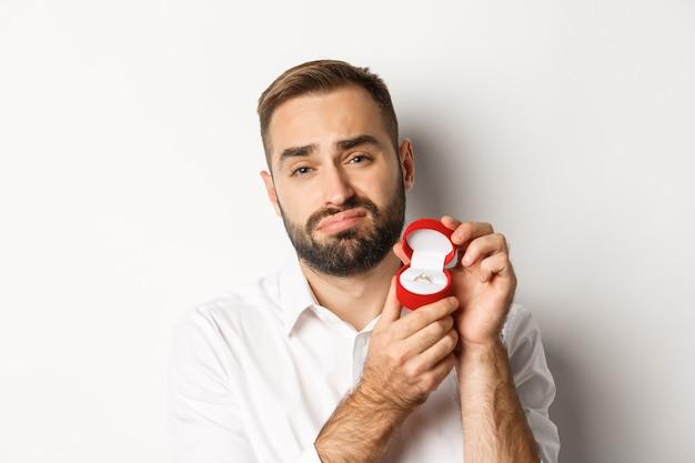 Primer plano de hombre esperanzado rogando casarse con él, con cara de tristeza y mostrando el anillo de bodas, haciendo una propuesta
