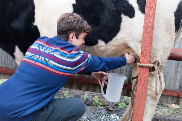 Primer plano de hombre feliz ordeñando a una vaca lechera
