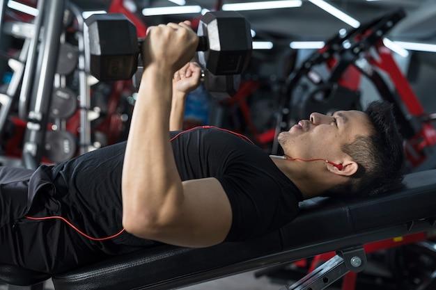 Primer plano de hombre de fitness, entrenamiento de chico atlético guapo con pesas