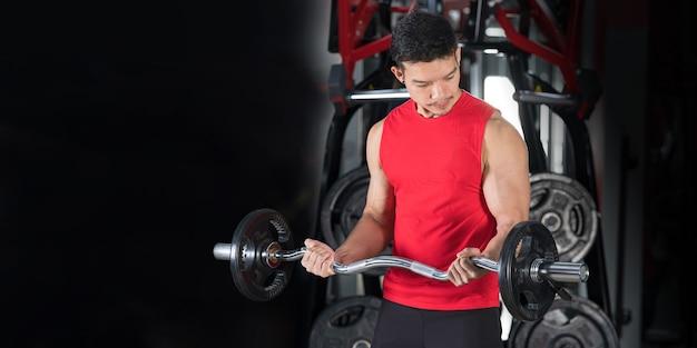 Primer plano de hombre de fitness, guapo atlético entrenamiento de levantamiento de pesas en el gimnasio