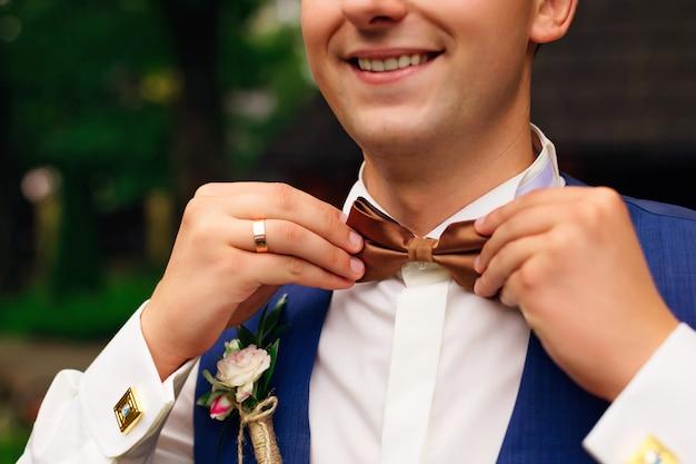Primer plano de hombre guapo adulto ajustando elegante pajarita marrón macho