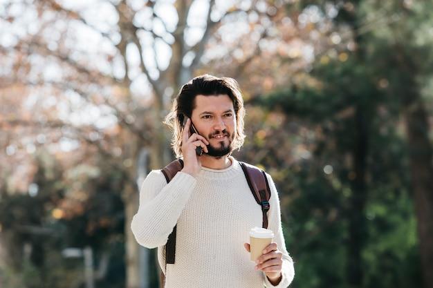 Primer plano de un hombre hablando por teléfono celular con café para llevar taza de papel