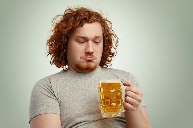 Primer plano de hombre indeciso con cabello pelirrojo sosteniendo un vaso de cerveza en sus manos