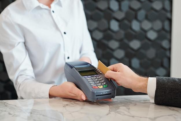 Primer plano del hombre irreconocible deslizando la tarjeta de crédito a través de la terminal de pago en la tienda u hotel
