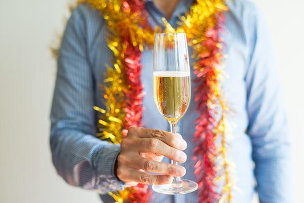 Primer plano del hombre irreconocible que sostiene la flauta de champán llena