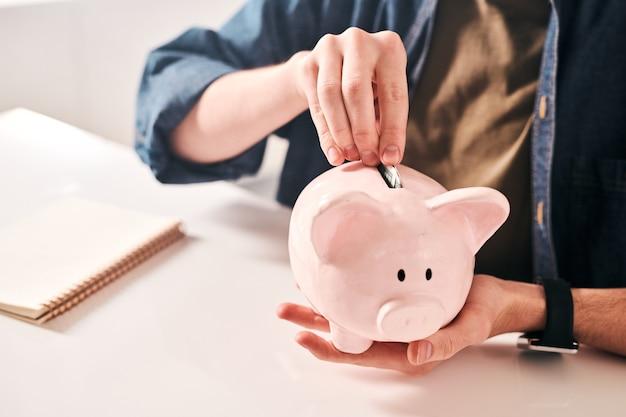 Primer plano de un hombre irreconocible sentado en la mesa y poniendo monedas en la alcancía mientras ahorra dinero en crisis