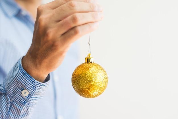 Primer plano de hombre irreconocible sosteniendo brillante bola de navidad