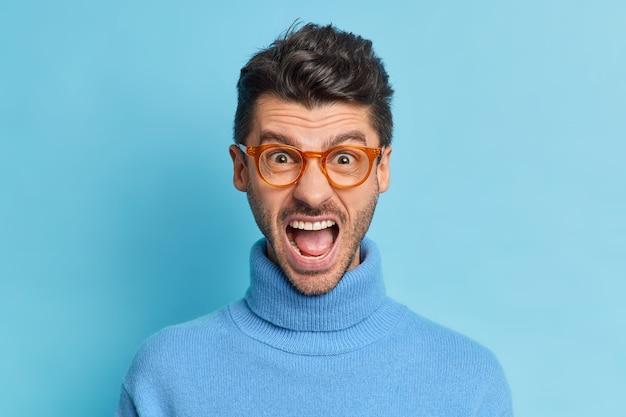 Primer plano de hombre irritado indignado mantiene la boca ampliamente abierta gritos con molestia expresa emociones negativas